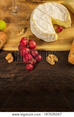 A photo of a camembert head at a wine tasting and pairing, with purple grapes, walnuts, and a glass