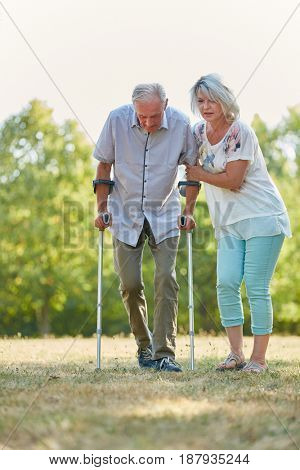 Old man lerns to walk with crutches in the nature with help from his geriatric nurse