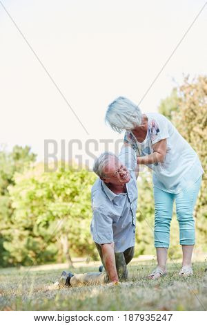 Senior woman helps man on his knees having a lumbago pain attack in the park in summer
