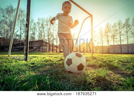 Boy playing with ball in football under sun light. Green field in city park a on sunny day.
