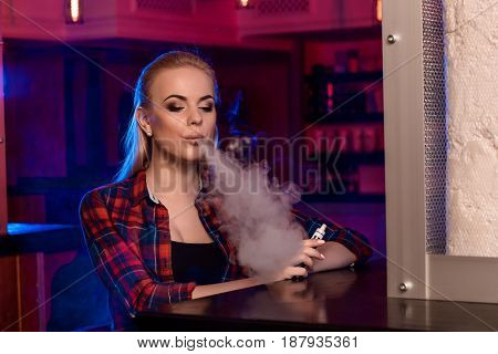 Young pretty woman in a shirt in a cage smoke an electronic cigarette at the vape bar. Vape shop.