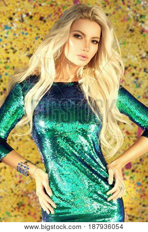 Young sexy woman wearing blue green shiny sheath dress with sequins, standing against yellow background. Party concept. Pretty slim blonde girl posing in sun light