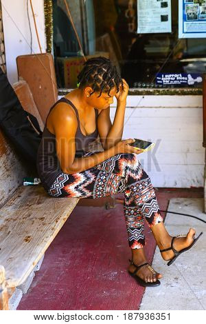 Clarksdale, MS, USA - 06/10/2015: Young black woman sitting outside a store in Clarksdale Mississippi using her cellphone