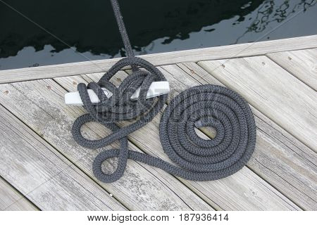 A rope tied to a cleat.  Rope coiled next to it
