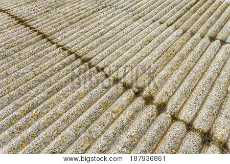 Asbestos cement sheets. Texture of old laid roofing sheets. Grey old roof.