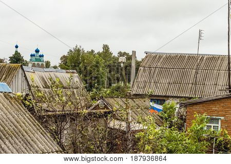 Roofs of the old beggar patriotic home ownership of the old Russian village. Russian flag in a ramshackle slum.
