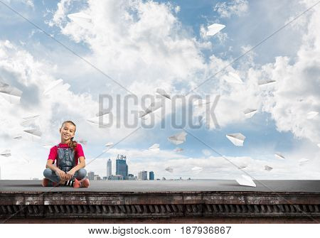 Cute kid girl sitting on building roof and looking in camera