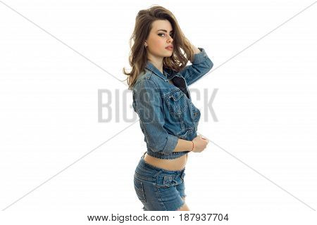 gorgeous young brunette is worth turning sideways in a jeans suit and looking at camera isolated on white background
