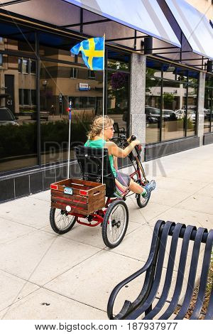 Fargo, ND, USA - 07/24/2015: Adult woman riding her tricycle with a Swedish flag pennant on the back on the streets of Fargo ND in the summer