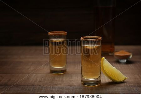 Golden tequila shots with lemon on wooden table