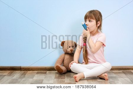 Cute little girl sitting on floor while using inhaler. Allergy concept