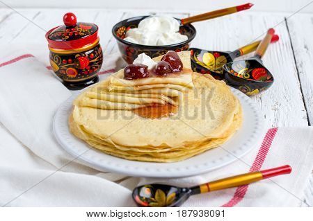 Fried thin pancakes with strawberry jam - traditional Russian dish. Selective focus.