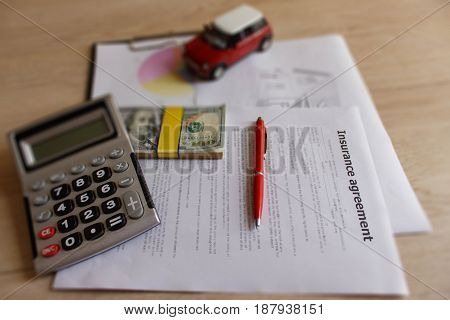 Car and Homeowner Insurance form with pen dollars calculator on the table. Insurance concept