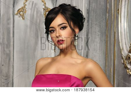 Pretty lady wearing pink ball gown or evening dress standing in luxury interior and looking at you.