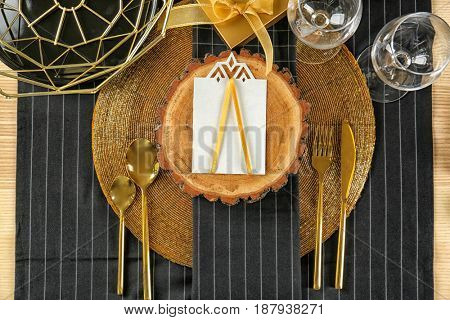 Table setting in black and gold color with floral decor on dark tablecloth