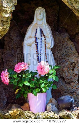 Virgin Mary Sculpture with rosaries next to roses where people can pray taken at a monastery