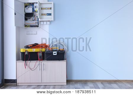 Distribution board with wires and tools on table in light room