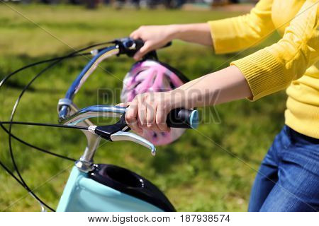 Young woman riding bike in park on sunny day