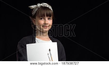 Portrait of young artist painter girl smiling to camera before black background, holding brushes and album