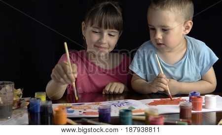 Kids holding brushes and painting by color gouache inks on white drawing album paper