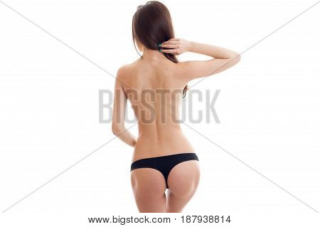 young slim naked girl stands with her back to the camera in black g-string with beautiful buttocks close-up isolated on white background