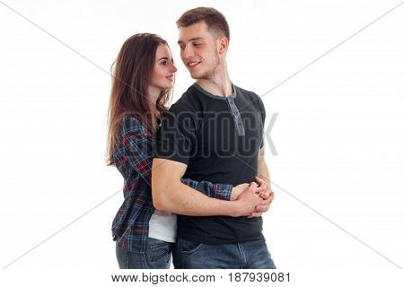 young cute girl romantic embraces the beautiful smiling guy in the back is isolated on a white background