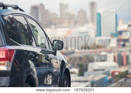 Rear view of black car with blurred city in the distance, looking at San Francisco.