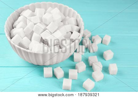 Bowl with sugar cubes on wooden table