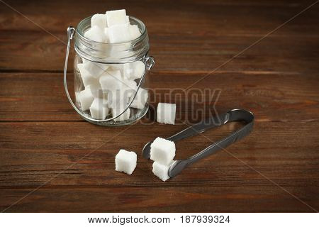 Glass jar with sugar cubes and forceps on wooden table