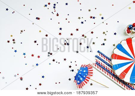 Festive red, white and blue picnic food supplies frame open space for copy with star confetti