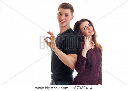 beautiful girl and a guy are standing back to each other smiling stare into the camera and show hands gestures isolated on white background