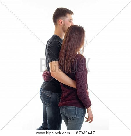 young tall guy keeps waist girl with long hair and they are turning back forward isolated on white background
