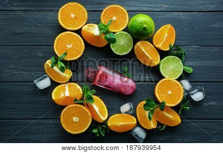 Delicious popsicle and citrus fruits on wooden table
