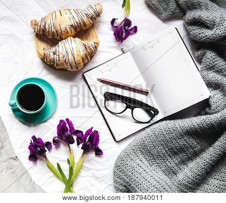 Breakfast in bed. Morning, croissant, coffee, flowers and a notebook with a pen. Planning