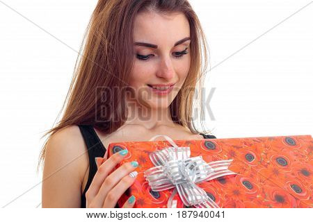 a charming young girl with long hair holds in her hand a great gift wrapping and smiling isolated on white background
