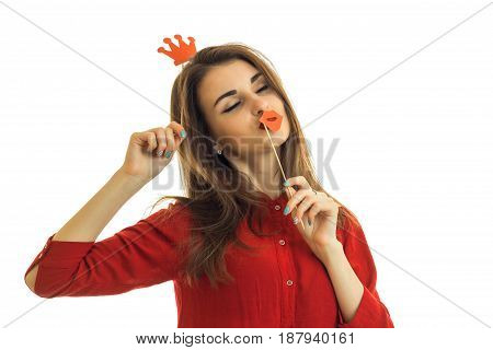 beautiful girl with dark hair is worth shutting your eyes and holding a paper Crown and a sponge is isolated on a white background