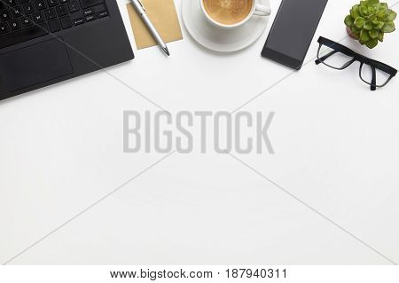 Directly above shot of laptop with coffee cup, eyeglasses and smartphone on white office desk