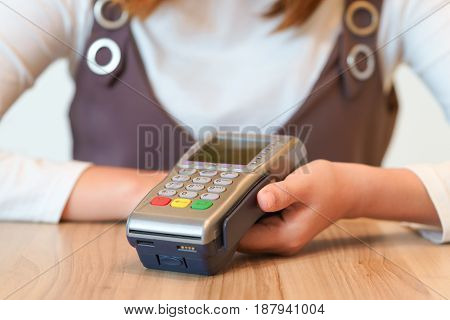 Woman hands get ready to paying with credit card swipe machine. concept