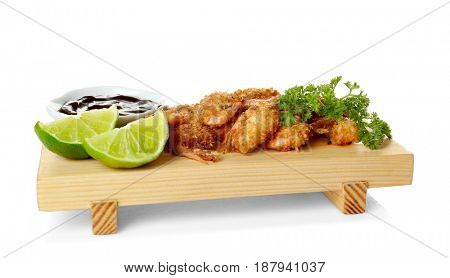 Wooden board with delicious coconut shrimps on white background