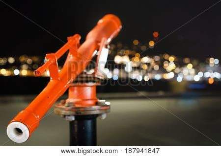 Telescope looking out into defocused lights producing bokeh. shallow depth of field shot. Metaphor of looking for direction Night time in Wellington New Zealand.