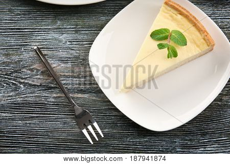 Plate with piece of tasty cheesecake on wooden table
