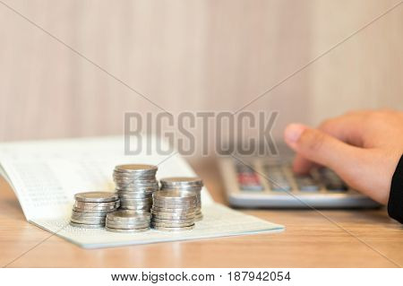 Hands of woman pushing on calculator with account book and coins