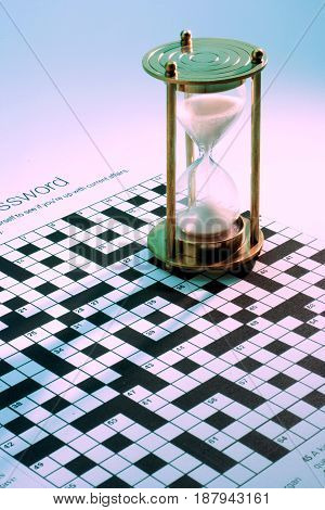 Hourglass on Crossword Puzzle on Blue and Pink Background