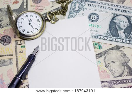 fountain pen empty paper and classic pocket watch on dollar banknote concept and idea of time value and money business and finance concepts.