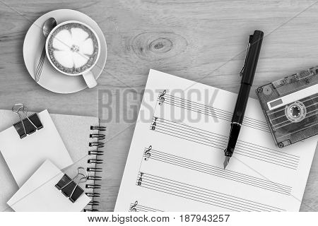 music sheet fountain pen tape cassette and coffee latte on wooden table top view picture