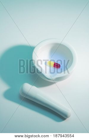 Pestle and Mortar with Pill on Blue Background