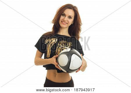 joyful charming young athlete stands upright looks into the camera and holds the ball isolated on white background