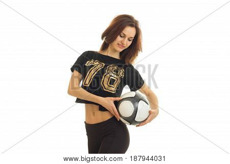Sweet young gymnast in black t-shirt holding a soccer ball looking down and smiling isolated on white background