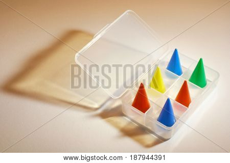 Game Pieces in Plastic Case on Warm Background