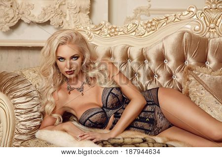 Beautiful Alluring Blond Woman In Sexy Lingerie Lying On Royal Sofa In Luxury Modern Interior. Beaut